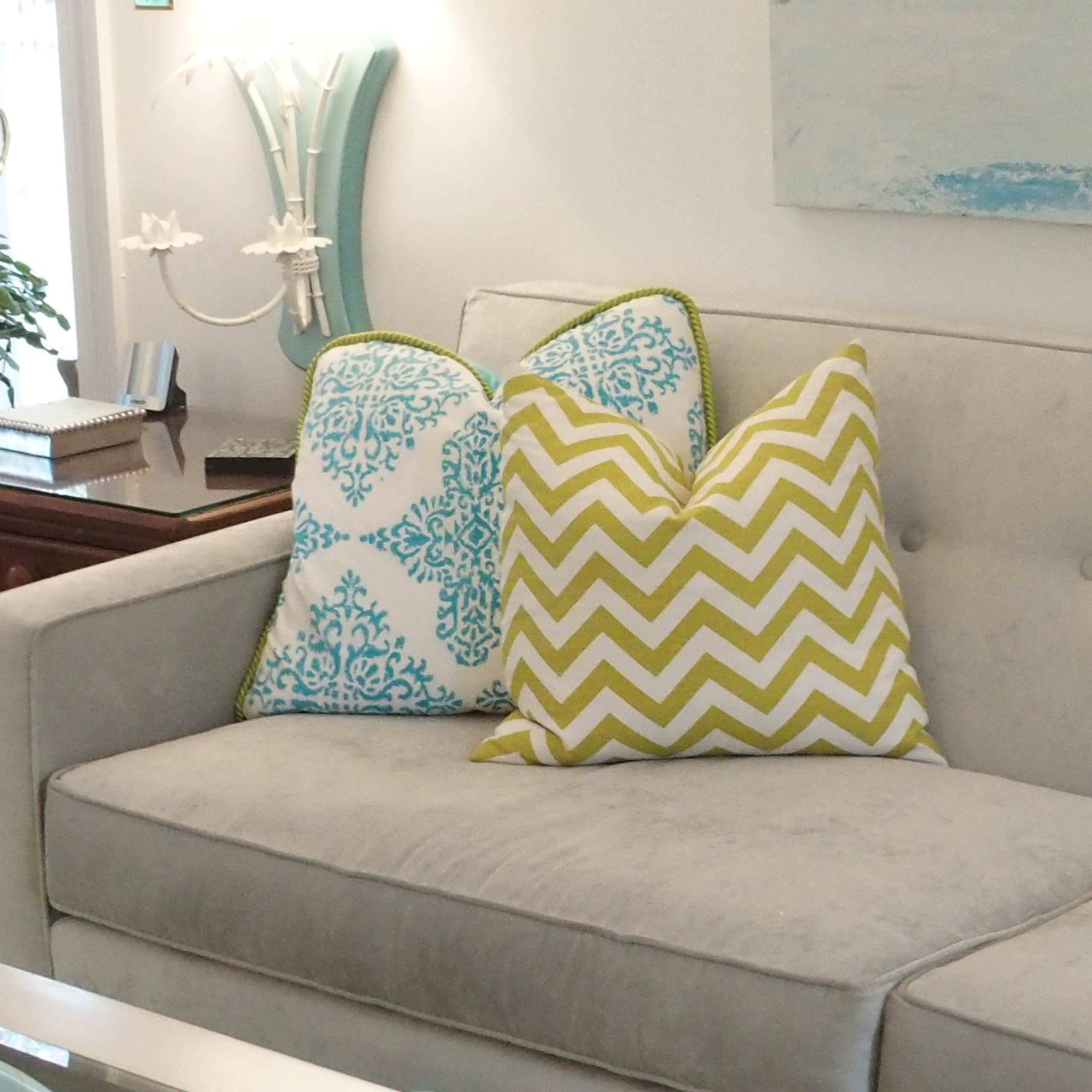 Living room with turquoise linen draperies, pearl gray sofa, citrus and white.