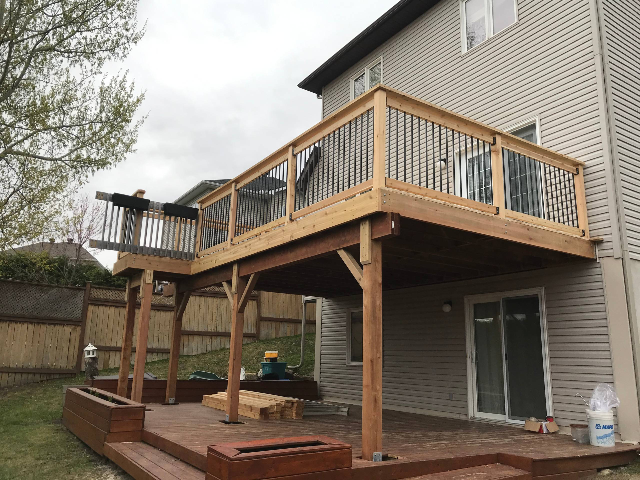 Walk-out red cedar deck with black round spindles
