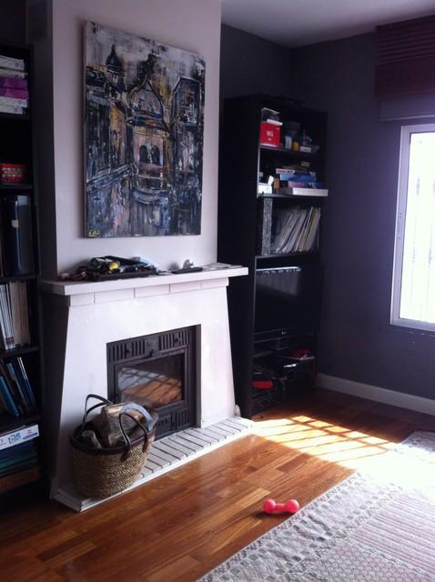 Foto de biblioteca en casa cerrada, ecléctica, pequeña, con paredes grises, suelo de madera en tonos medios, chimenea tradicional y marco de chimenea de yeso