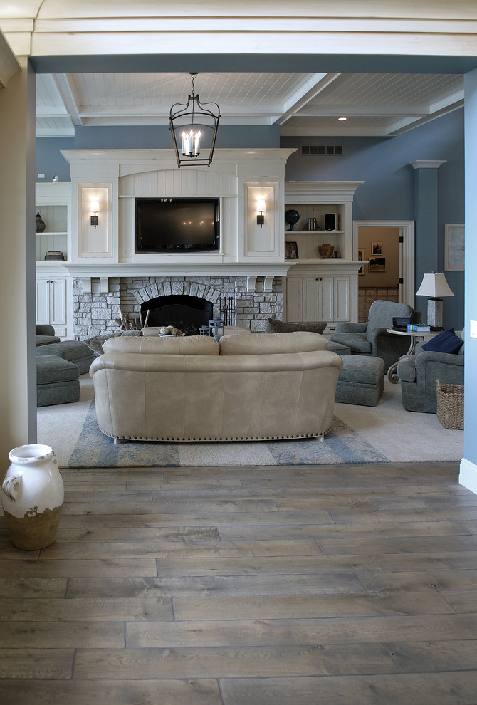 Huge beach style medium tone wood floor, brown floor and vaulted ceiling living room photo in Chicago with blue walls, a standard fireplace, a stone fireplace and a media wall