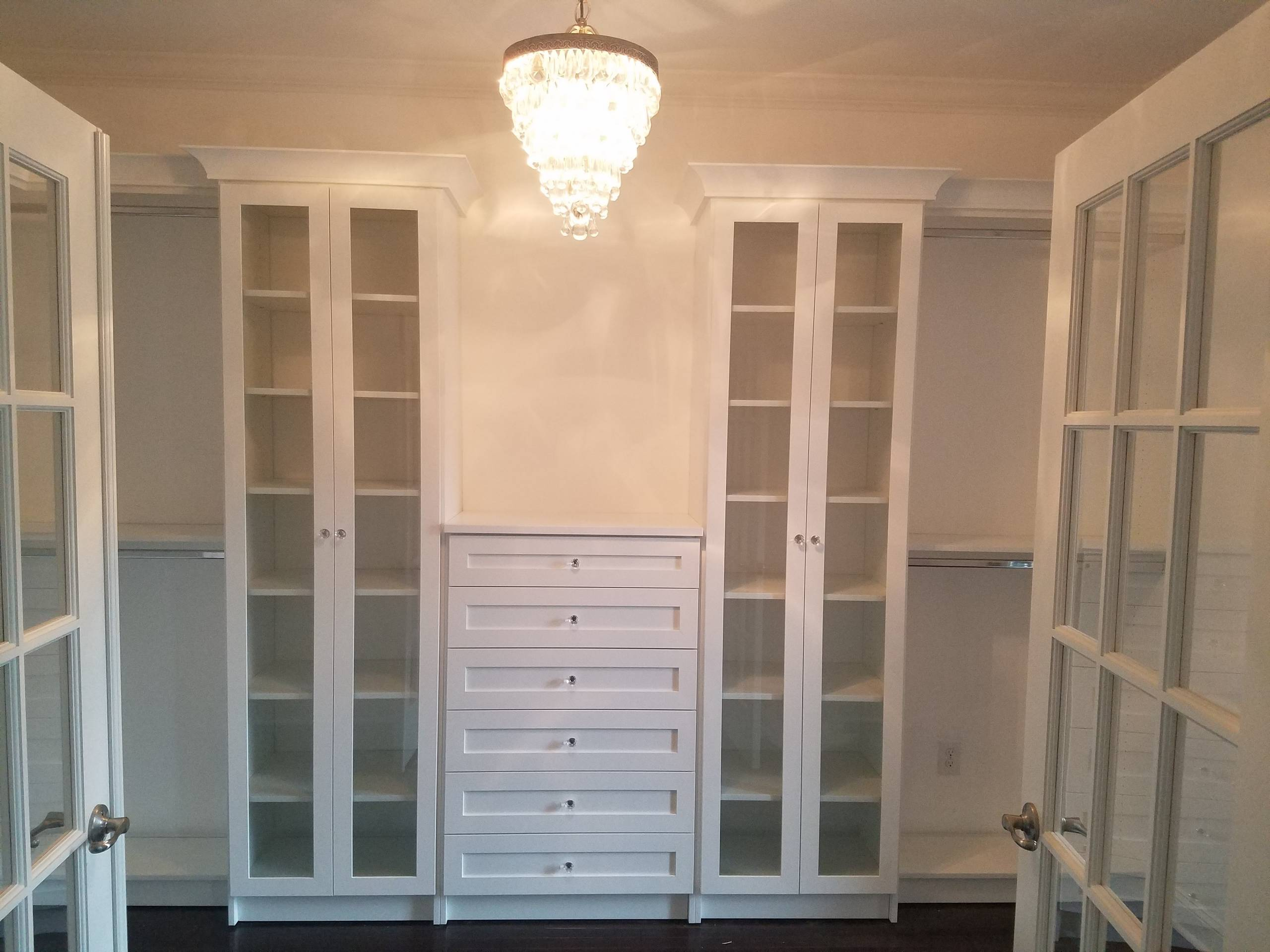 White walk in closet with shaker style drawer fronts and crown molding.  Also includes glass cabinets