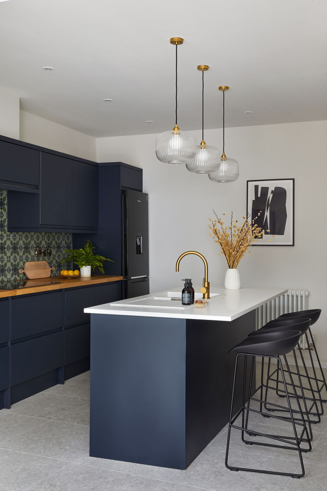 Medium sized contemporary galley kitchen/diner in Other with a double-bowl sink, flat-panel cabinets, blue cabinets, composite countertops, green splashback, ceramic splashback, stainless steel appliances, porcelain flooring, an island, white floors, multicoloured worktops and feature lighting.