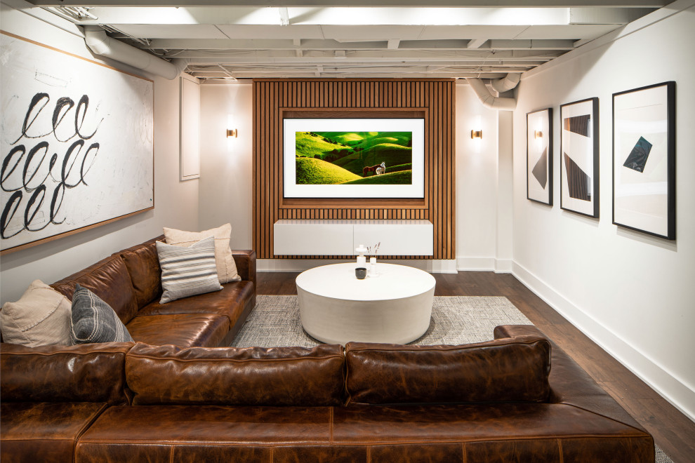 Inspiration for a mid-sized modern underground vinyl floor, brown floor and wood wall basement remodel in Columbus with a home theater and white walls