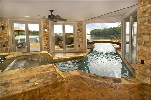 Indoor pool and hot tub with a slide  Lake House Pool with a 40' vanishing edge and a carved concrete ...