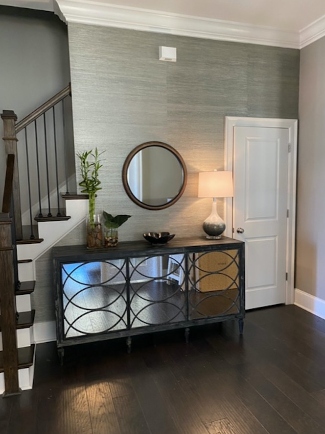 Maximizing a foyer space which in most homes would contain maybe just a bench that would turn unto a secondary dropzone. The mirrors of course make a space seem bigger. But note the mix of description