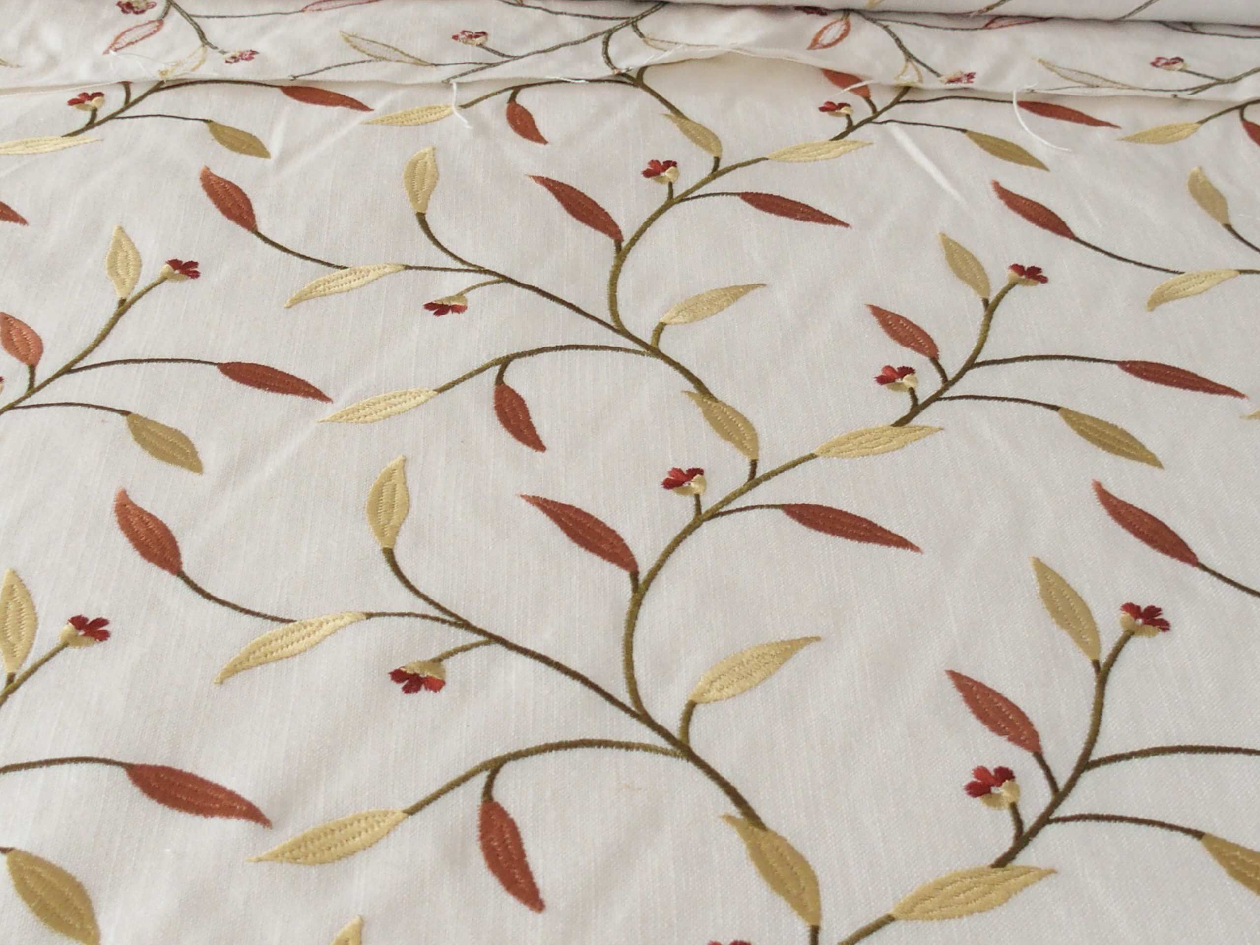 Bedroom draperies in offwhite linen blend with embroidered leaves.