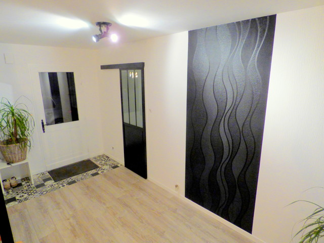 Cette photo montre un grand hall d'entrée moderne avec un mur noir, sol en stratifié et un sol gris.