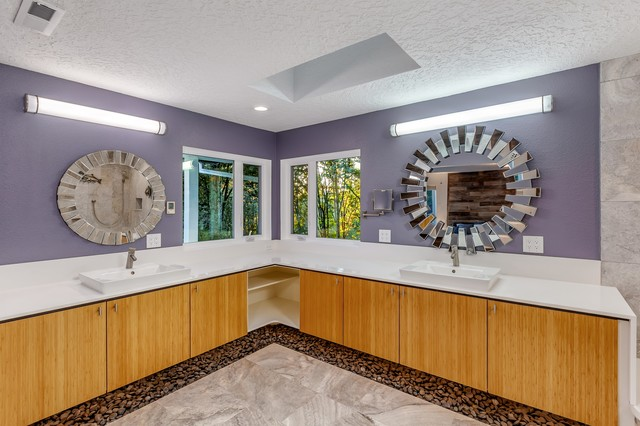 Bathroom - large modern master gray tile and stone tile travertine floor and gray floor bathroom idea in Portland with flat-panel cabinets, light wood cabinets, a one-piece toilet, purple walls, an integrated sink, engineered quartz countertops and white countertops