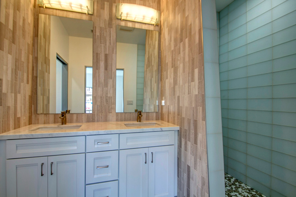 Doorless shower - large contemporary beige tile and stone tile doorless shower idea in San Diego with an undermount sink, white cabinets and marble countertops