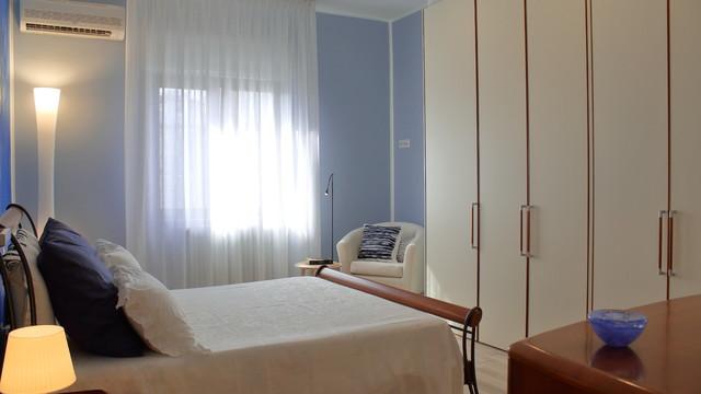 Foto di una grande camera matrimoniale minimal con pareti blu e pavimento in gres porcellanato