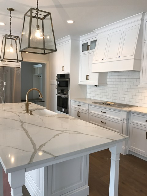 Example of a mid-sized farmhouse medium tone wood floor and brown floor kitchen design in Cleveland with a farmhouse sink, recessed-panel cabinets, white cabinets, quartzite countertops, white backsplash, subway tile backsplash, stainless steel appliances and an island