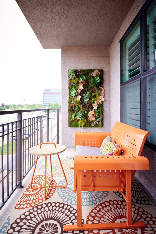 petit balcon avec mobilier orange et mur végétalisé