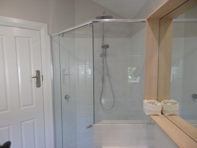 Foto di una grande stanza da bagno padronale scandinava con ante lisce, ante in legno chiaro, vasca da incasso, doccia ad angolo, piastrelle bianche, pareti bianche, lavabo sottopiano, top in quarzo composito e porta doccia a battente