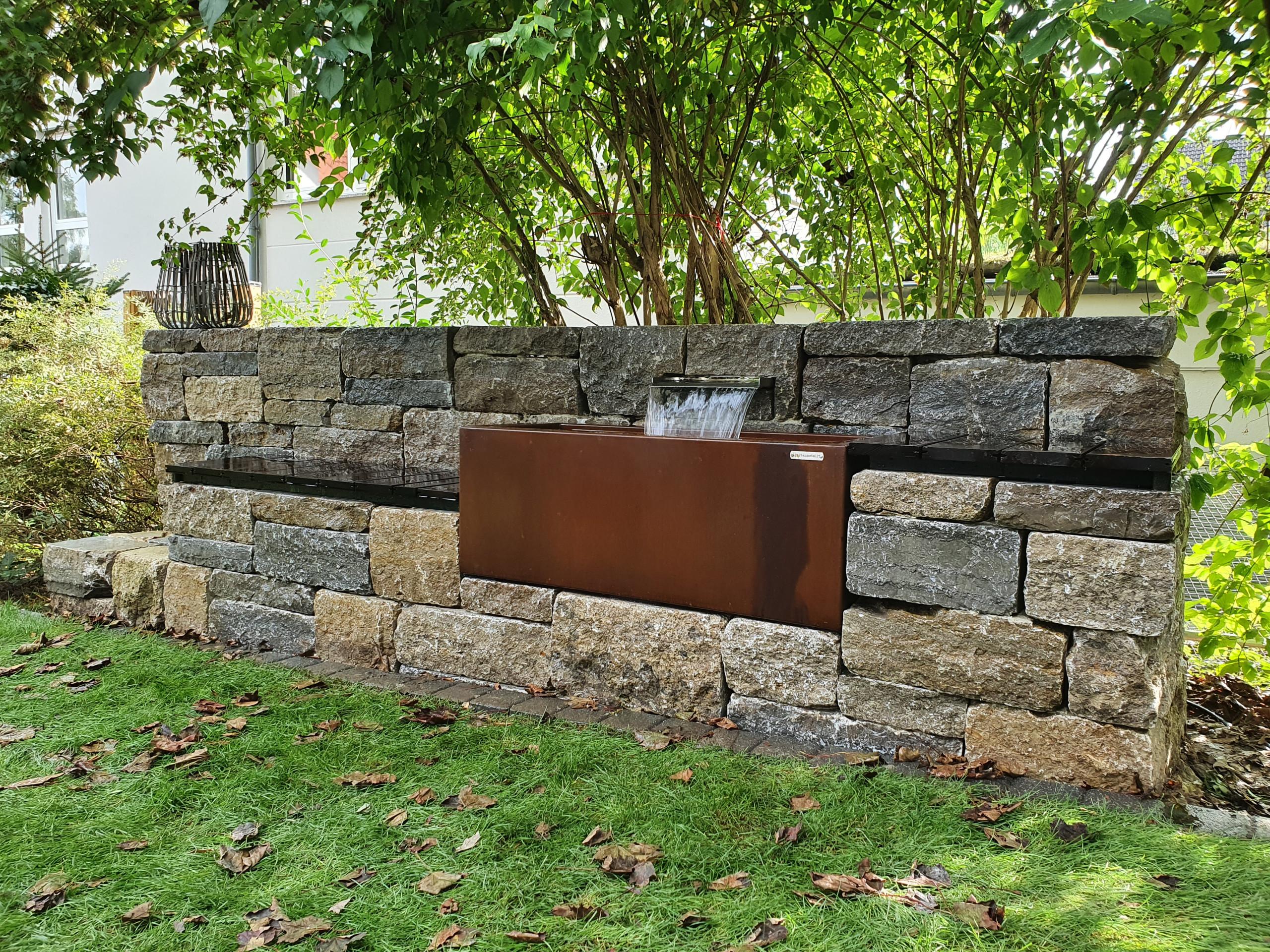 Natursteinmauer mit Wasserspiel und Sitzgelegenheiten