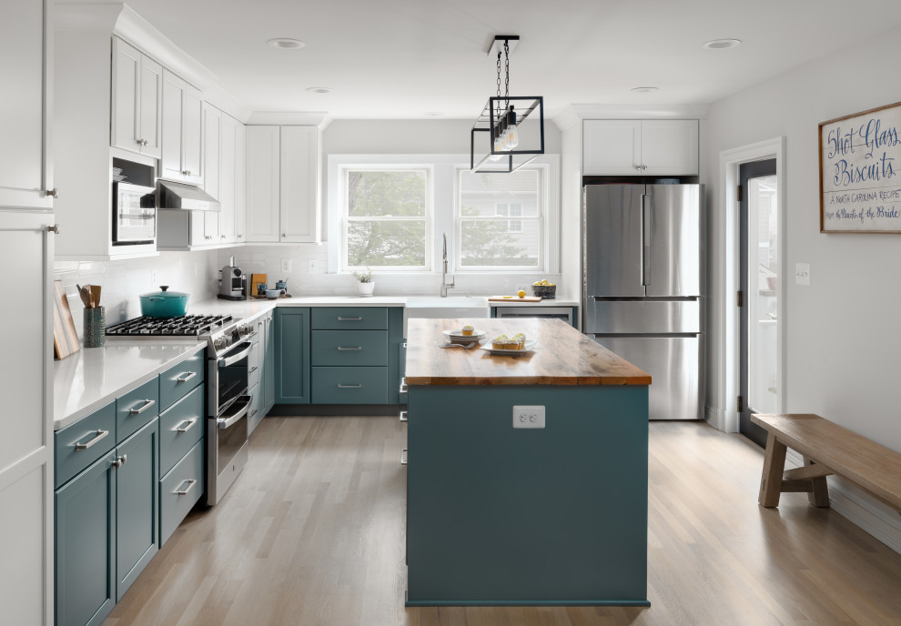 Mid-sized transitional l-shaped light wood floor and exposed beam kitchen photo in DC Metro with a farmhouse sink, shaker cabinets, green cabinets, quartz countertops, white backsplash, ceramic backsplash, stainless steel appliances, an island and white countertops