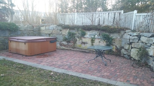 Outdoor Brick Patio With Crumbling Granite Wall.
