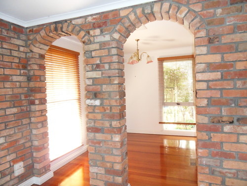 Living Room Wall With 2 Smaller Archways Looking Into Dining Which Can Also Be Accessed Via Kitchen To The Right Of Fireplace
