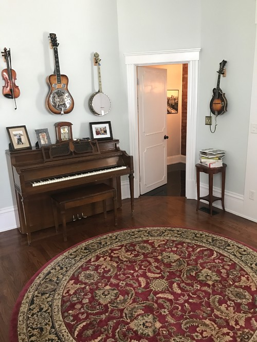The Dining Room Also Has A Red Rug And Dark Furniture. The Living Room Has  A Charcoal Couch With A Beige And Light Grey Rug With Dark Wood Furniture.