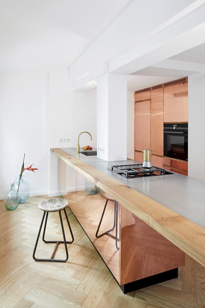 Offene, Mittelgroße Moderne Küche mit integriertem Waschbecken, Betonarbeitsplatte, braunem Holzboden, Kücheninsel, braunem Boden und grauer Arbeitsplatte in Berlin
