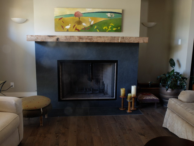 Example of a mid-sized eclectic dark wood floor family room design in Edmonton with beige walls, a standard fireplace, a wood fireplace surround and no tv