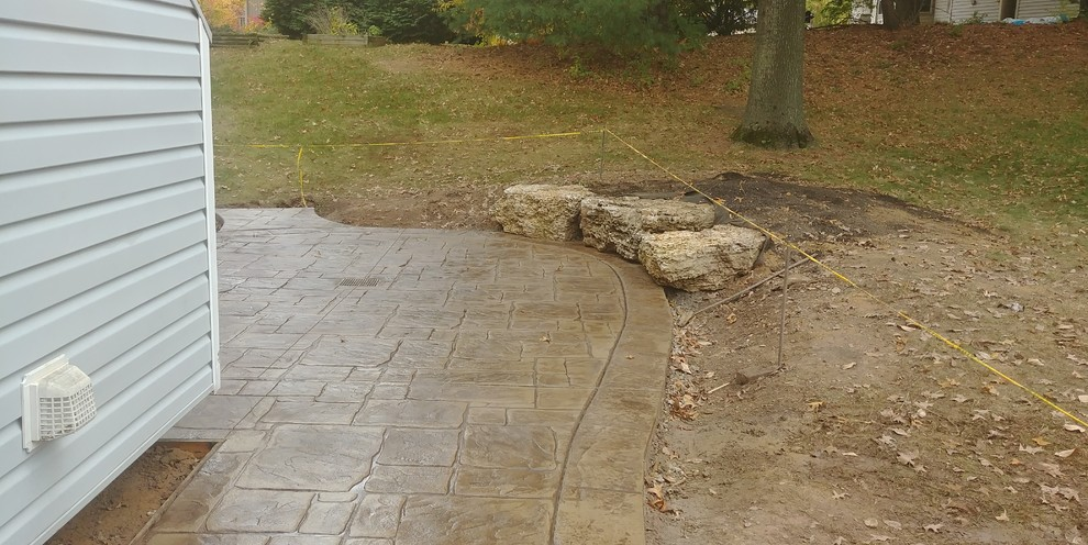 Stamped Concrete Patio with limestone boulder sitting wall in St Charles Missour