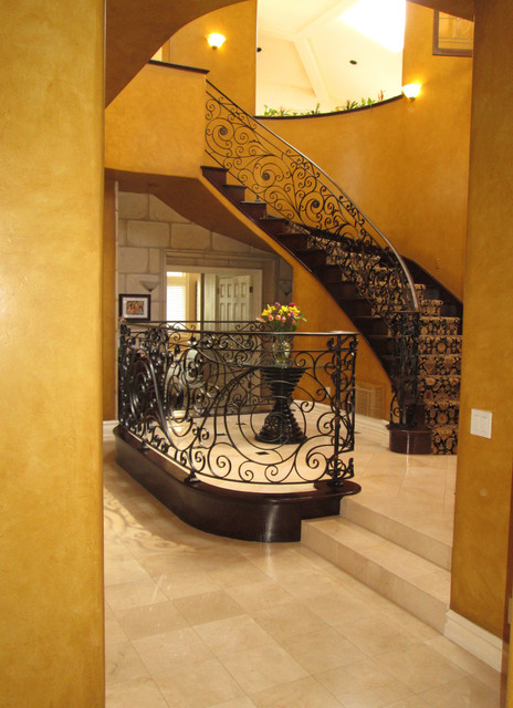 Example of a large tuscan foyer design in Orange County with orange walls