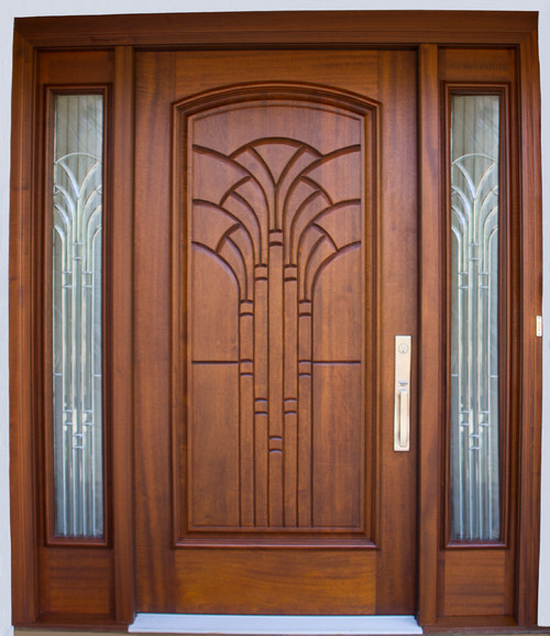 Single Flat Front Door Made From A Light Stained Mahogany Featuring Ornate Carvings And Decorative Side Glass Panels