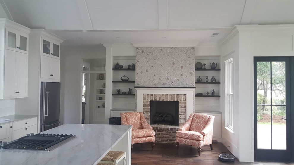 Inspiration for a mid-sized beach style formal and open concept medium tone wood floor living room remodel in San Diego with white walls, a standard fireplace, a brick fireplace and no tv