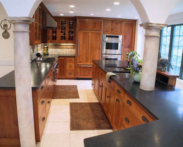 Example of a tuscan kitchen design in Boston with glass-front cabinets, a double-bowl sink, medium tone wood cabinets, granite countertops and paneled appliances