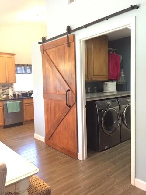 Single sliding barn door installed raw steel painted black for Sliding laundry door