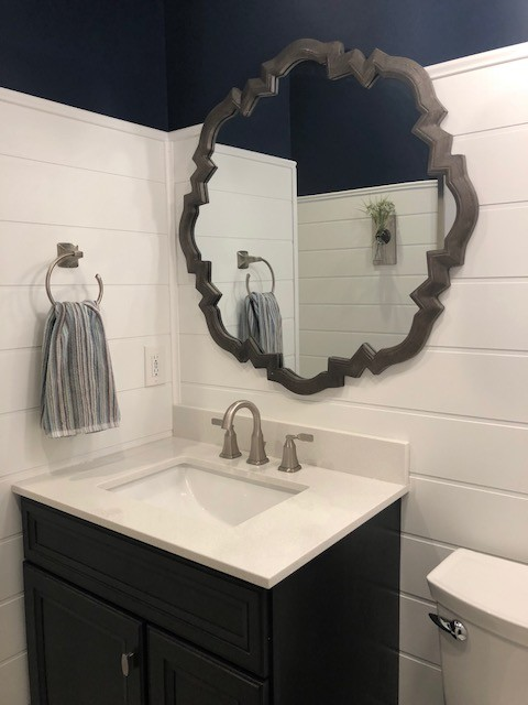 Inspiration for a mid-sized transitional 3/4 porcelain floor and beige floor bathroom remodel in DC Metro with recessed-panel cabinets, black cabinets, a two-piece toilet, blue walls, an undermount sink, engineered quartz countertops and white countertops