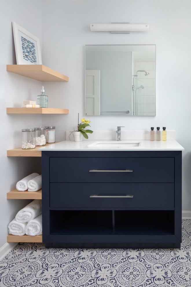 Mid-sized trendy kids' white tile and porcelain tile porcelain tile, multicolored floor and single-sink alcove shower photo in Other with flat-panel cabinets, blue cabinets, a two-piece toilet, blue walls, an undermount sink, quartz countertops, a hinged shower door, white countertops, a niche and a freestanding vanity