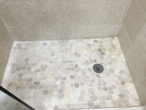 While the contractor did slant the floor towards the drain  we still get a  good deal of water between some stones that doesn t drain away. Help  Pebble Tile   Grout Problems