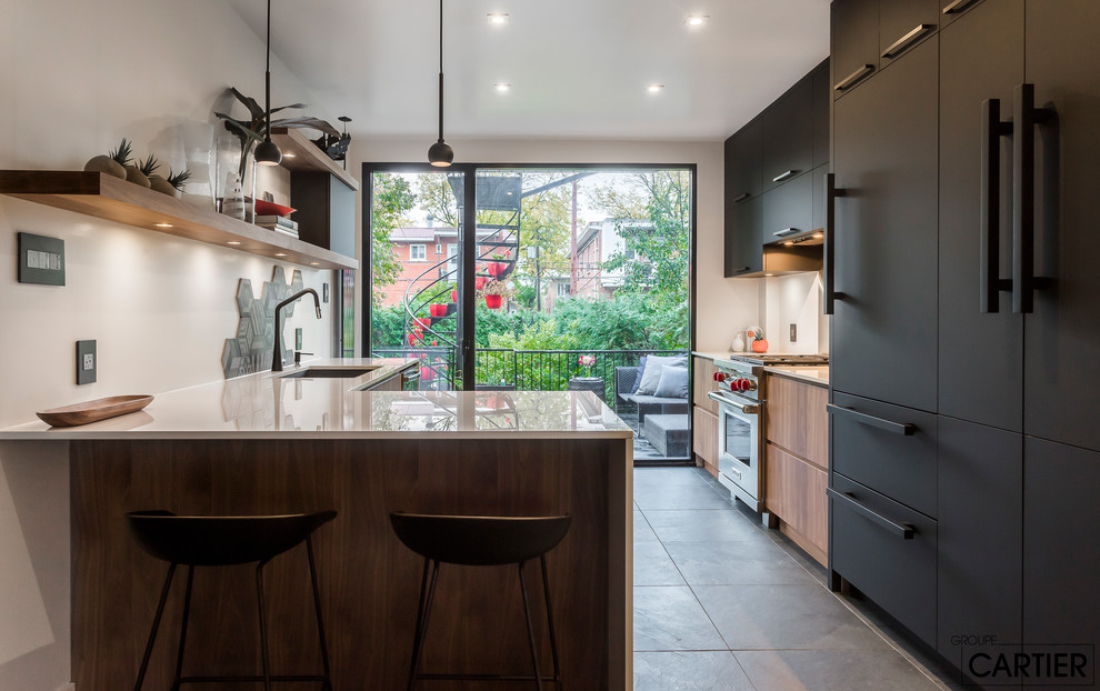 Open concept kitchen - mid-sized modern galley slate floor and black floor open concept kitchen idea in Montreal with an undermount sink, flat-panel cabinets, black cabinets, solid surface countertops, gray backsplash, ceramic backsplash, stainless steel appliances and a peninsula