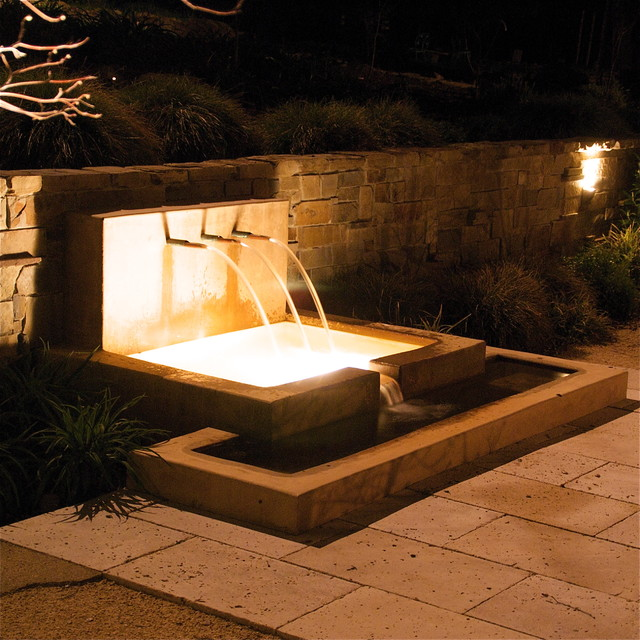 Fountain At Night With Stone Retaining Wall Modern Patio
