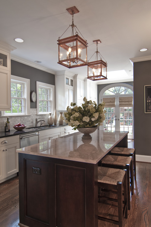 Housekaboodle -Kitchen by Carolina Design Associates has popular color on the walls. Island counter is Calcutta gold marble. Lantern shape gives a nod to the windows