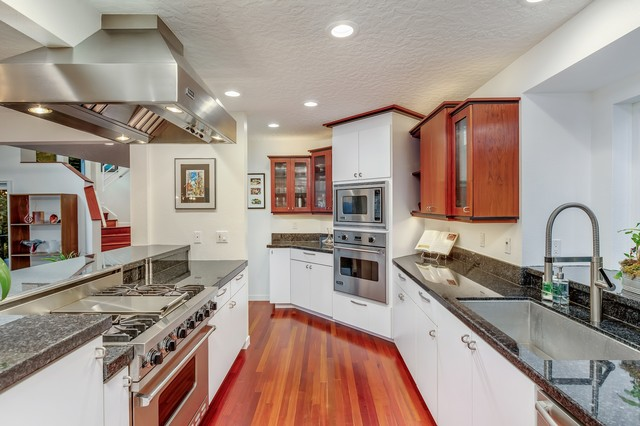 Inspiration for a mid-sized modern galley dark wood floor and multicolored floor eat-in kitchen remodel in Portland with a single-bowl sink, flat-panel cabinets, white cabinets, granite countertops, black backsplash, stone slab backsplash, stainless steel appliances and black countertops
