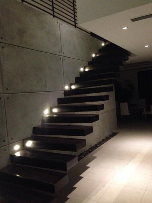 Escalera volada revestida en madera Pared de cemento visto
