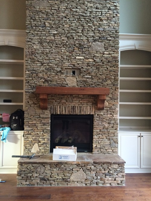 I have an open concept home. The living has a stacked stone fireplace. The kitchen has off-white shaker style cabinets to the ceiling