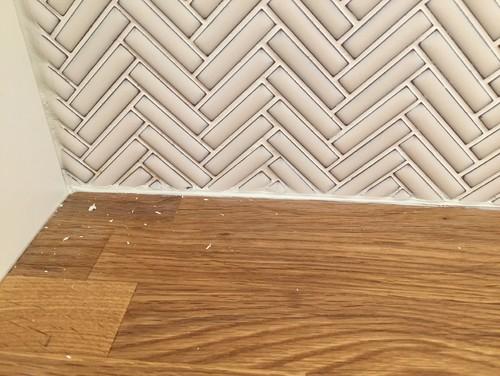 Messy Edge Where Mosaic Tile Backsplash Meets Wood Counter