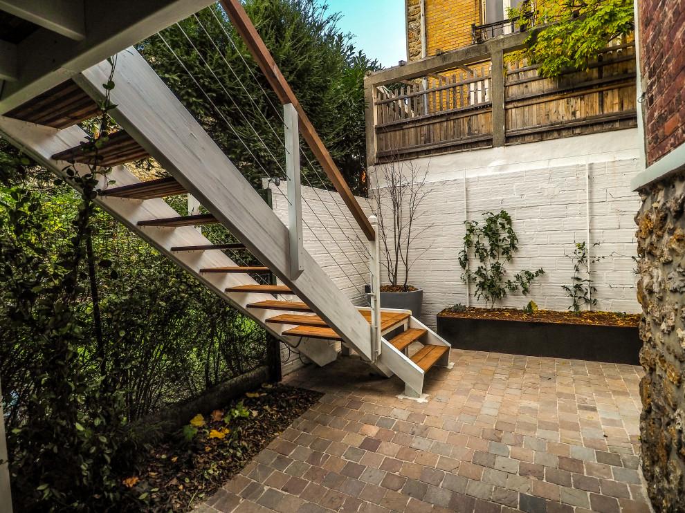 Foto di una terrazza design di medie dimensioni, in cortile e al primo piano con un pontile, una pergola e parapetto in materiali misti