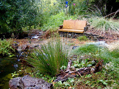 Pond > Bermed-Earth Seatwall with Repurposed Concrete Sidewalk Chunk