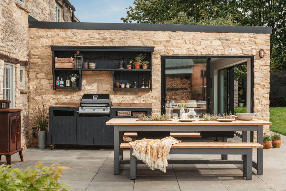 Inspiration for a large country backyard stone patio kitchen remodel in Gloucestershire