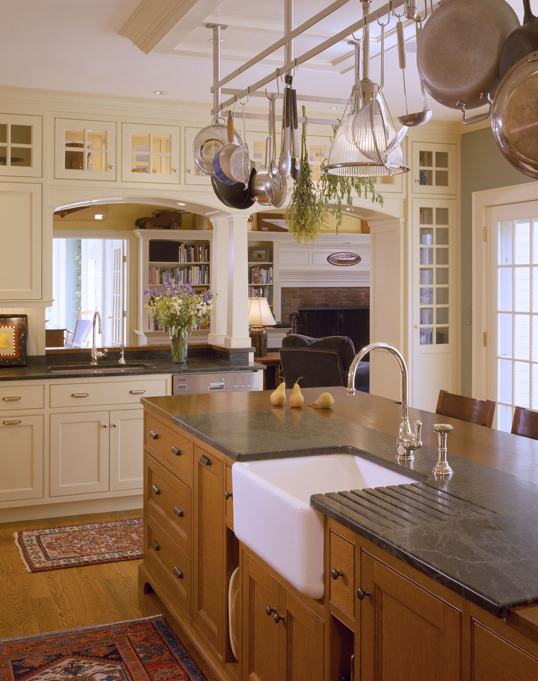 Eat-in kitchen - mid-sized traditional u-shaped light wood floor eat-in kitchen idea in Other with soapstone countertops, a farmhouse sink, medium tone wood cabinets, recessed-panel cabinets, white backsplash, stone slab backsplash, stainless steel appliances and an island