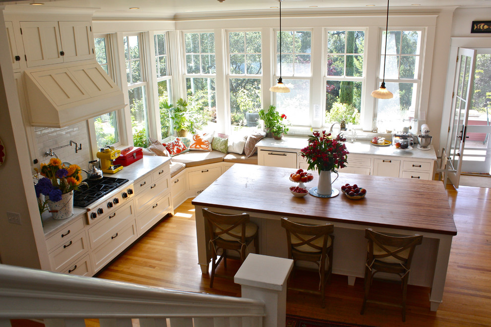 Elegant kitchen photo in San Francisco with wood countertops, white cabinets and stainless steel appliances