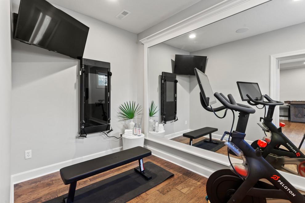 Großer Klassischer Fitnessraum mit grauer Wandfarbe, hellem Holzboden und braunem Boden in Kansas City