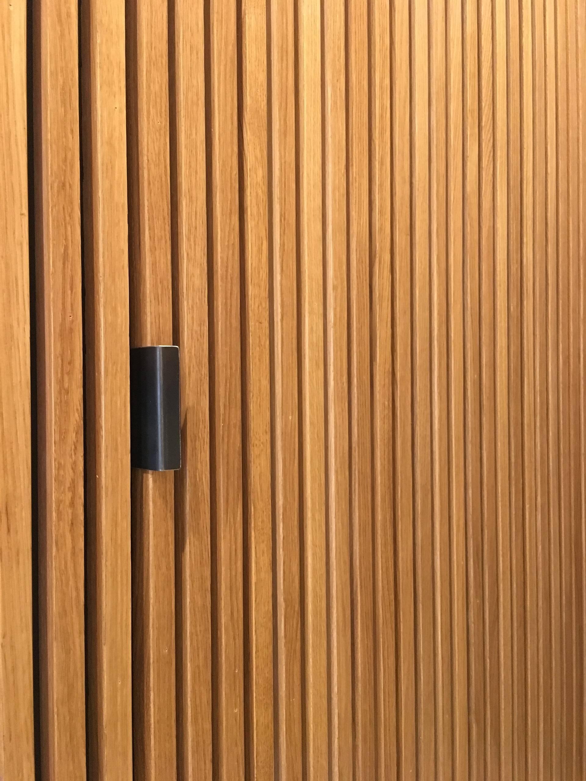 Detalle de puerta oculta en el volumen revestido con madera