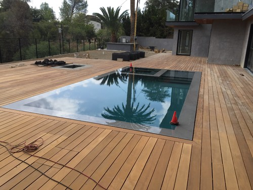 Ipe deck flowing outside flush around infinity edge pool.