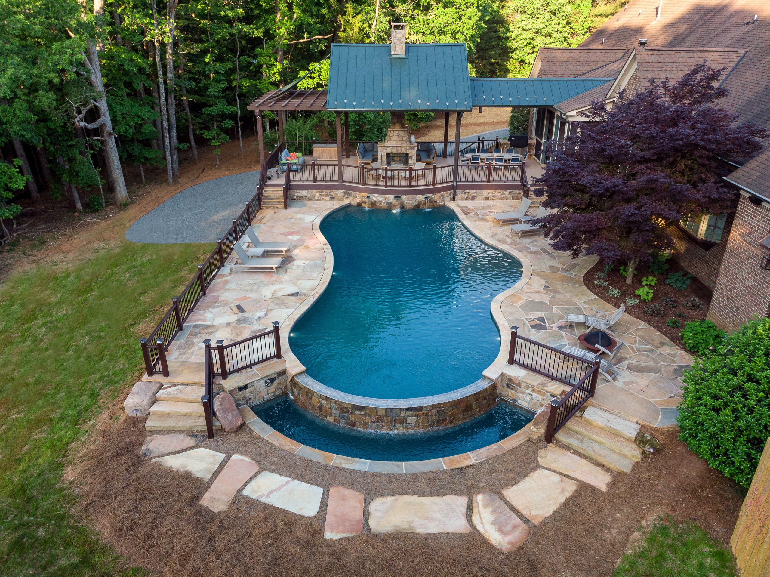 Luxury vanishing edge pool with copper scuppers