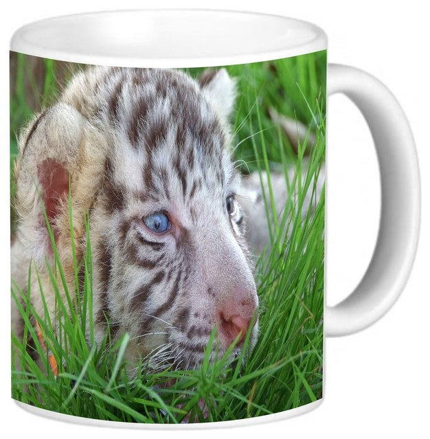 baby white tiger in grass with bright blue eyes coffee mug